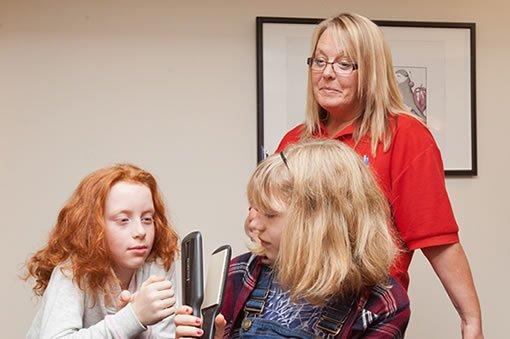 Volunteer looking at two girls holding hair tongs