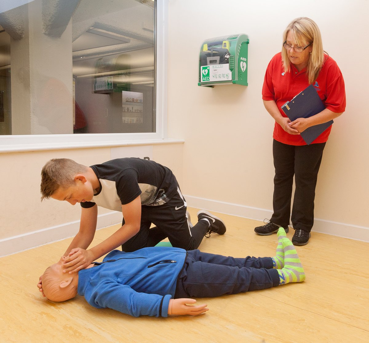 A boy learns resuscitation techniques and is leaning over a dummy of a child